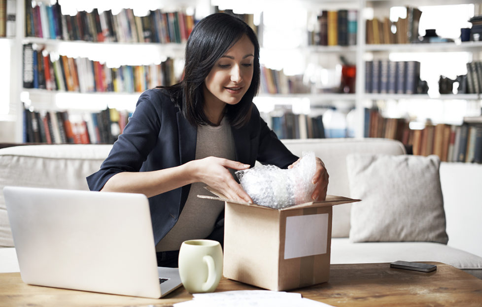 Woman preparing parcel for shipment in her cozy loft apartment