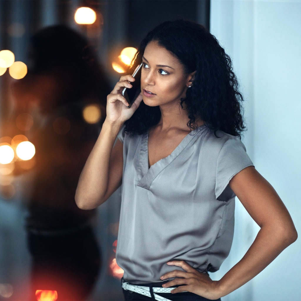 Elegant woman on phone, looking concerned, looking out of window at night time city