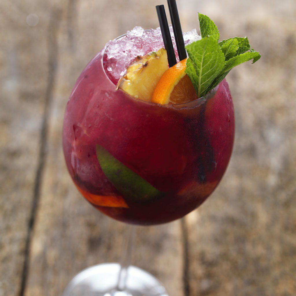 Glass of red coloured mocktail with citrus slices and mint garnish