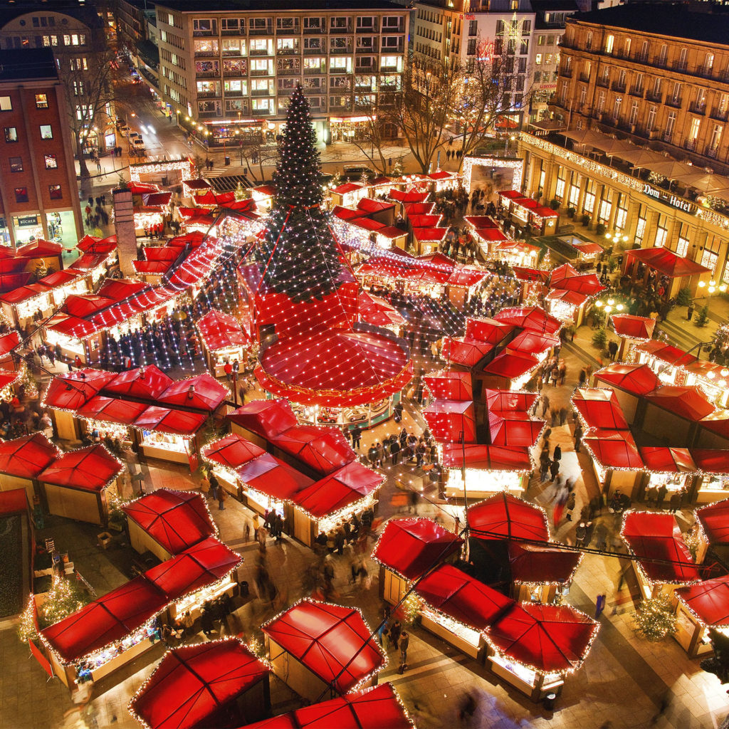 Aerial view of fairylit, red-roofed market stalls in square around giant Christmas tree