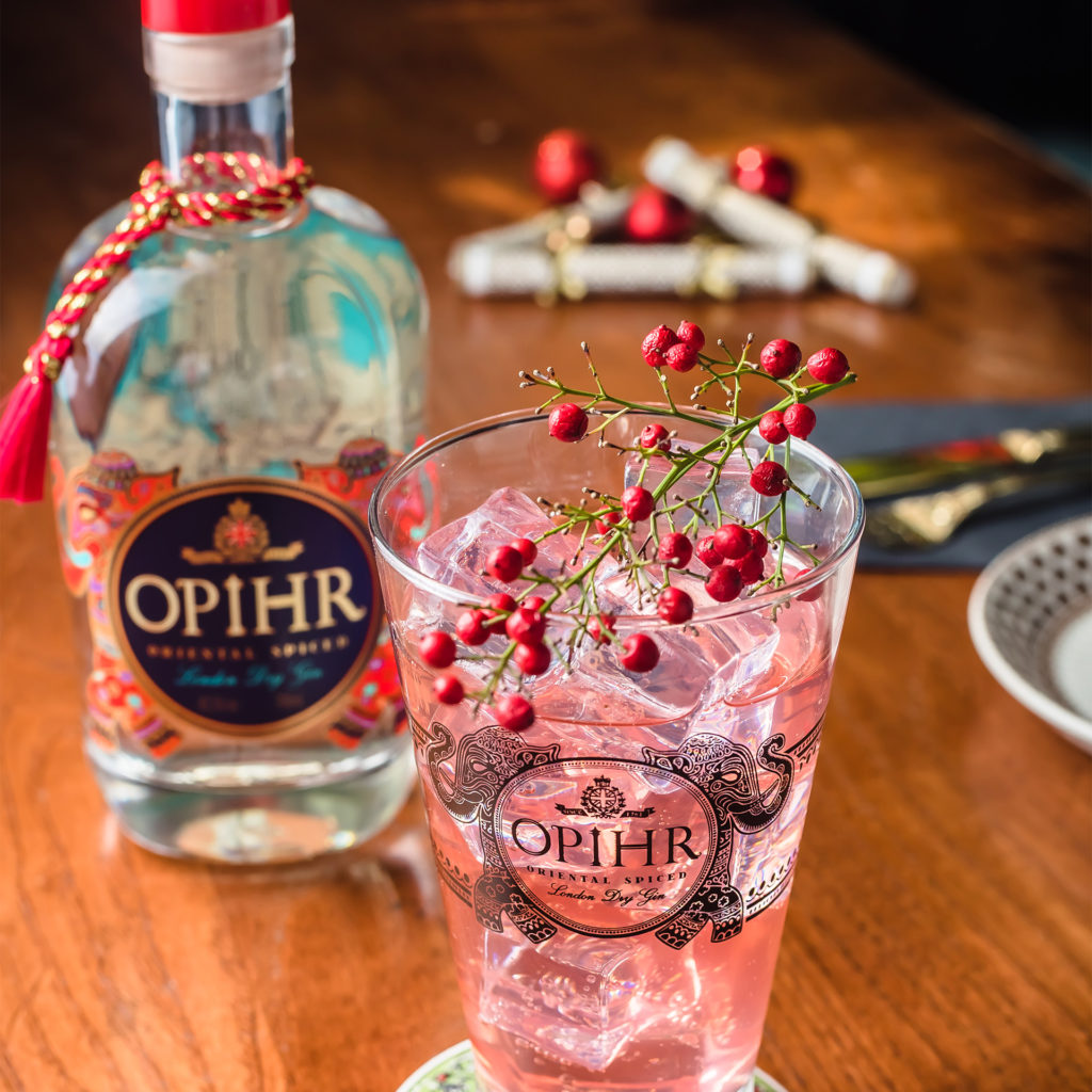 Tall glass with ice, pink drink and cranberries on stalk, bottle of Opihr gin behind