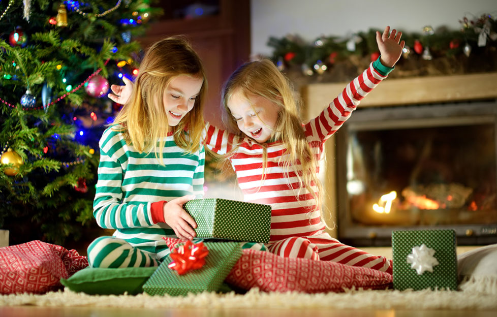 Two little girls opening Christmas parcel Pic: Istockphoto