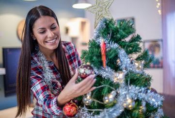 Lady decorating beautiful Christmas tree Pic: Istockphoto