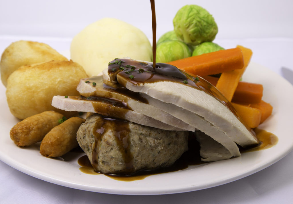 Traditional British Christmas dinner turkey mashed potatoes, sprouts, battened carrots, roast potatoes,ham,stuffing and cocktail sausages with gravy being added