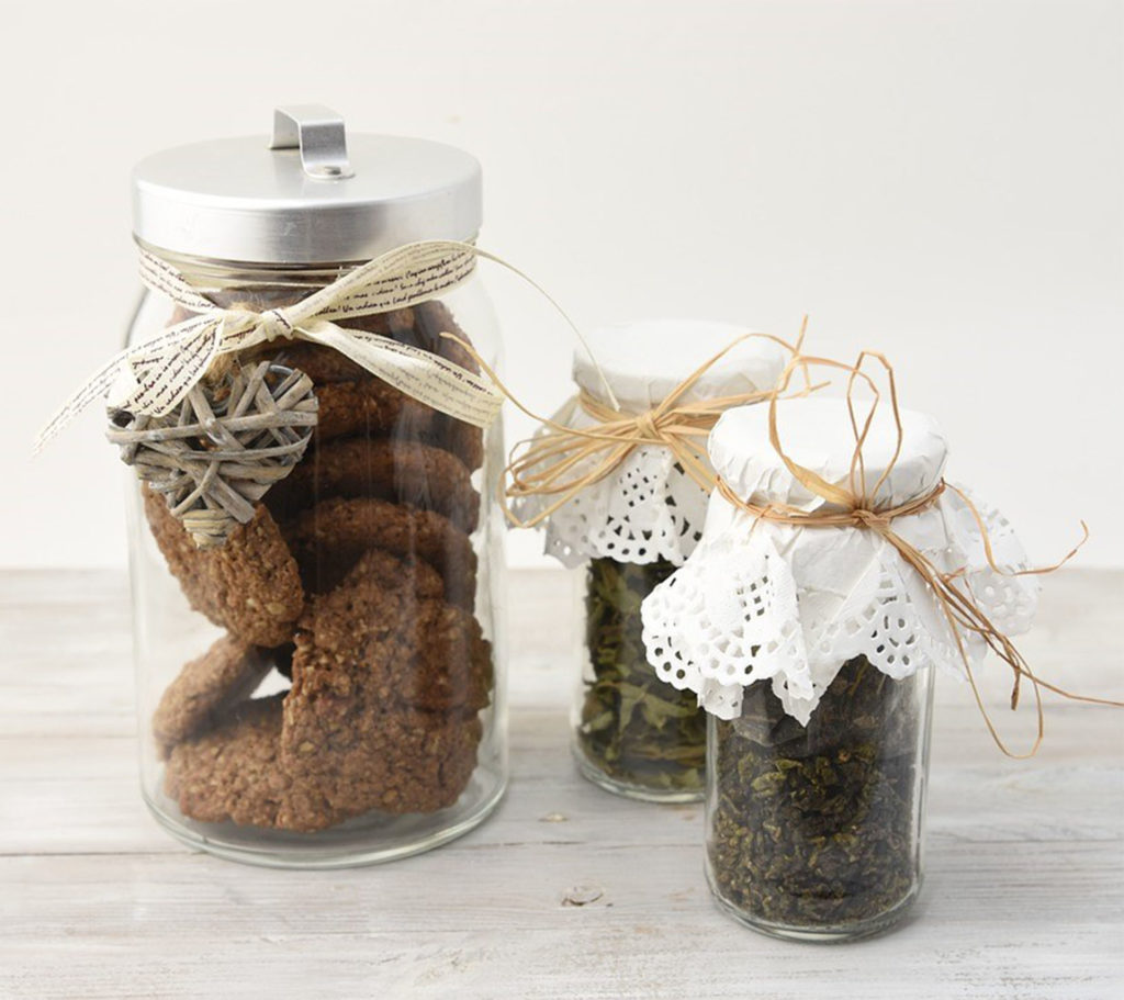 One jar of biscuits and two of jam/chutney, with paper doilies tied with string on top of the lid