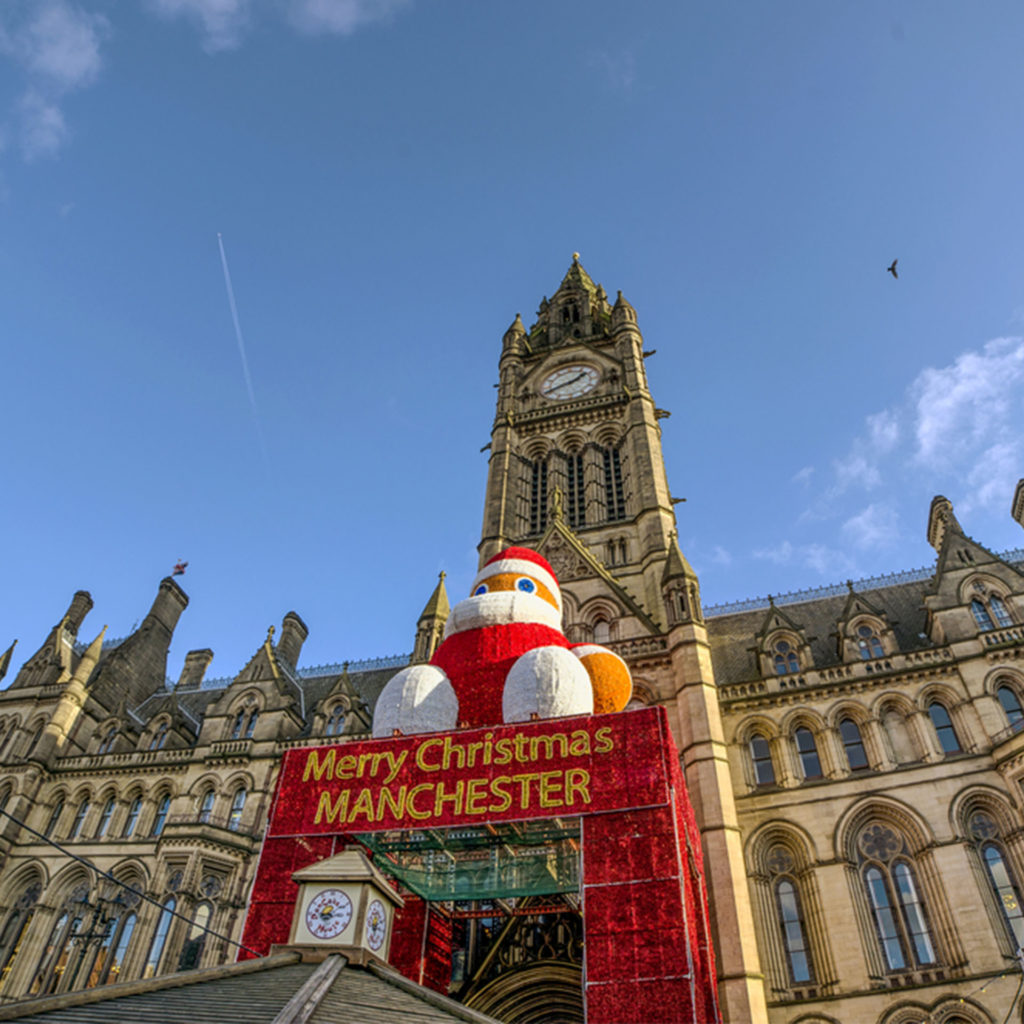 "Giant inflatable Santa figure sits on canopy over entrance with message ""Merry Christmas Manchester"", town hall behind"