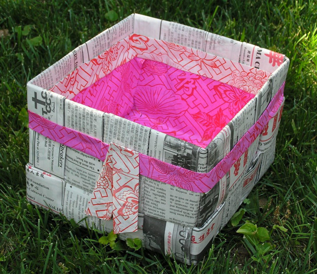 Box covered in newspaper and lined with bright pink paper