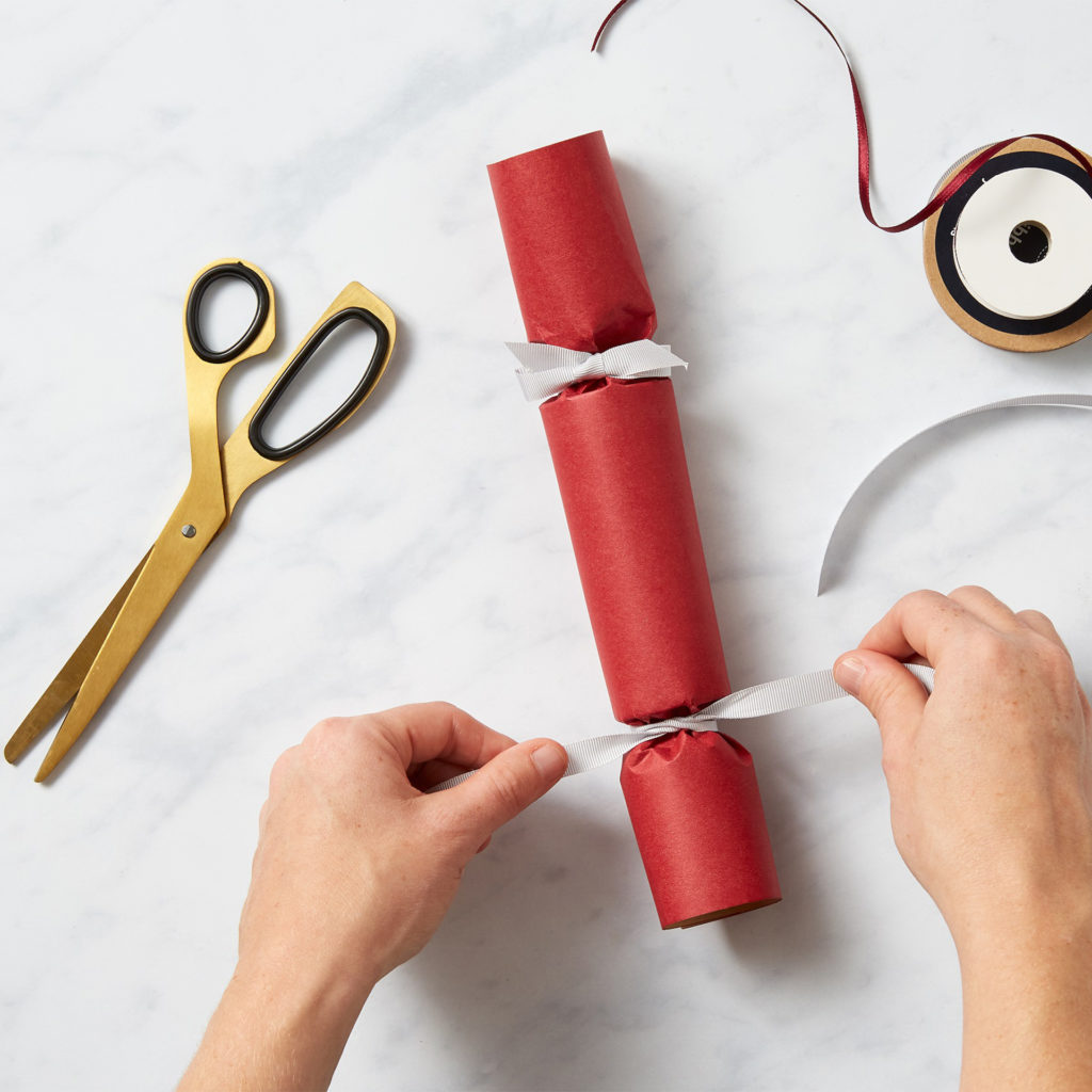 Tying ribbon around paper tube, either side of central cardboard tube, to make a recognisable cracker.