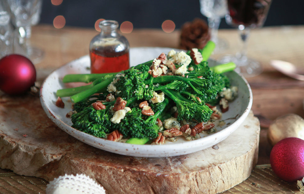Broccoli, pecans and blue cheese on a serving plate with small glass jar of maple dressing, all on board made of a slice of tree trunk