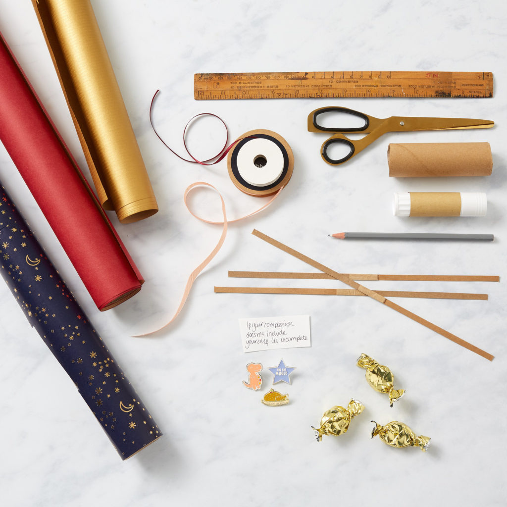 Materials for making Christmas crackers: paper, scissors, pencil, ruler, ribbon, cracker snaps and small items to fill