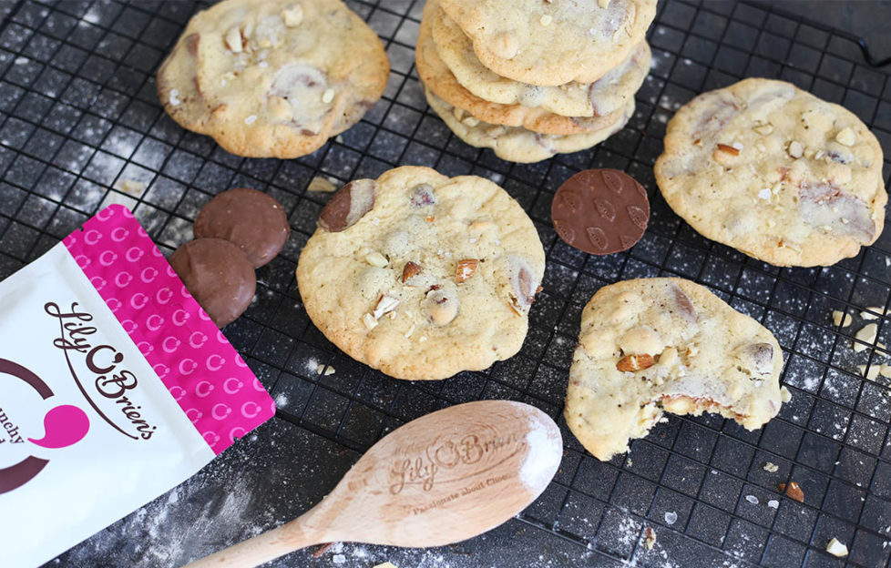 Freshly made choc chunk cookies on cooling rack with wooden spoon and extra choc buttons