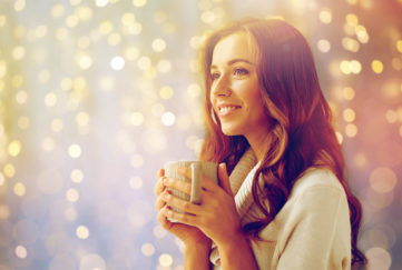 Woman in cosy cream jumper holding mug enjoys atmosphere of soft fairylights