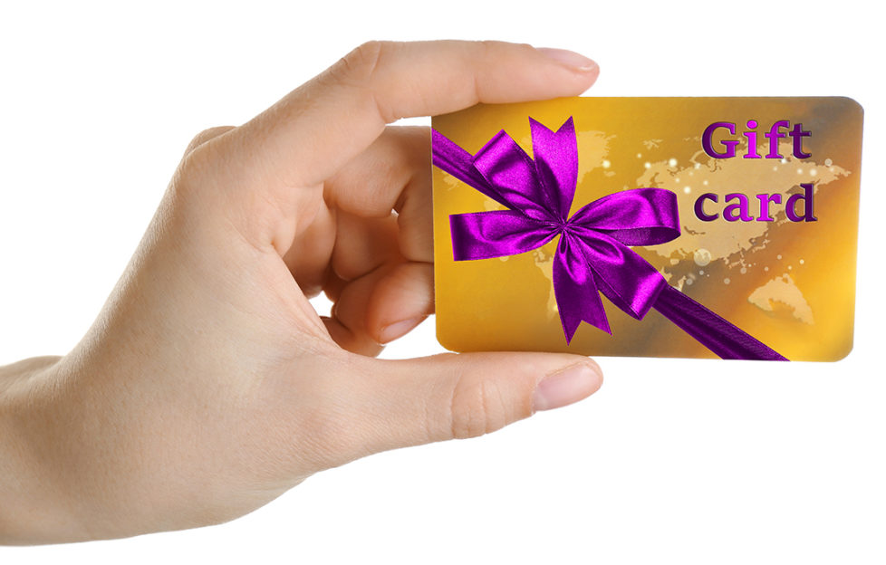 Woman's hand holding gift card decorated with purple ribbon