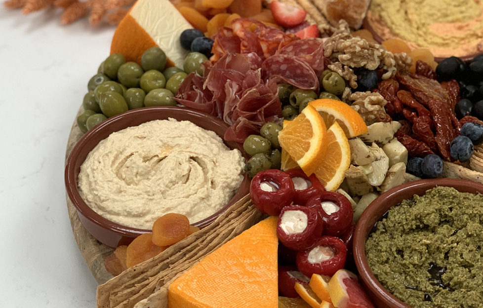 Grazing platter with olives, cured meat, cheese, stuffed peppers, orange slices and dishes of dip,