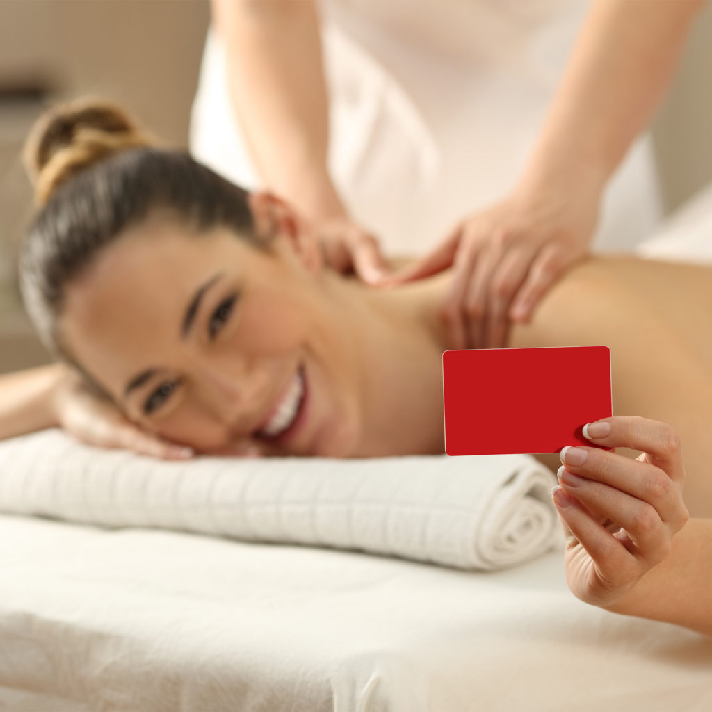 Woman enjoying shoulder massage at spa holding out gift card