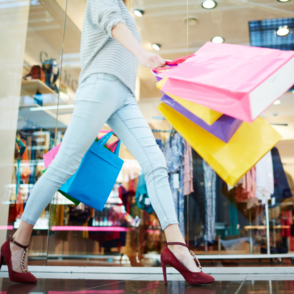 Low angle shot of woman striding along swinging a handful of shopping bags