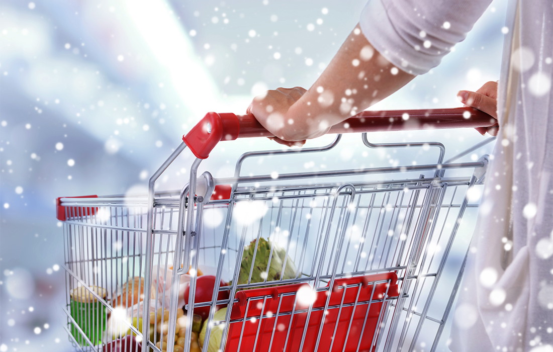 Save money on Christmas food shopping - woman pushing supermarket trolley, half full of Christmas food, snow falling