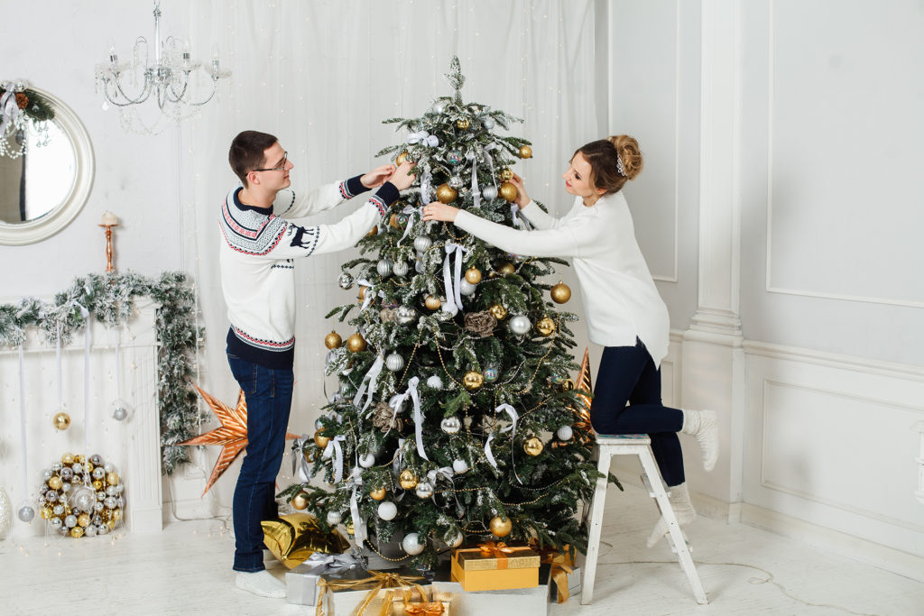 Woman on small ladder and man decorating Christmas tree