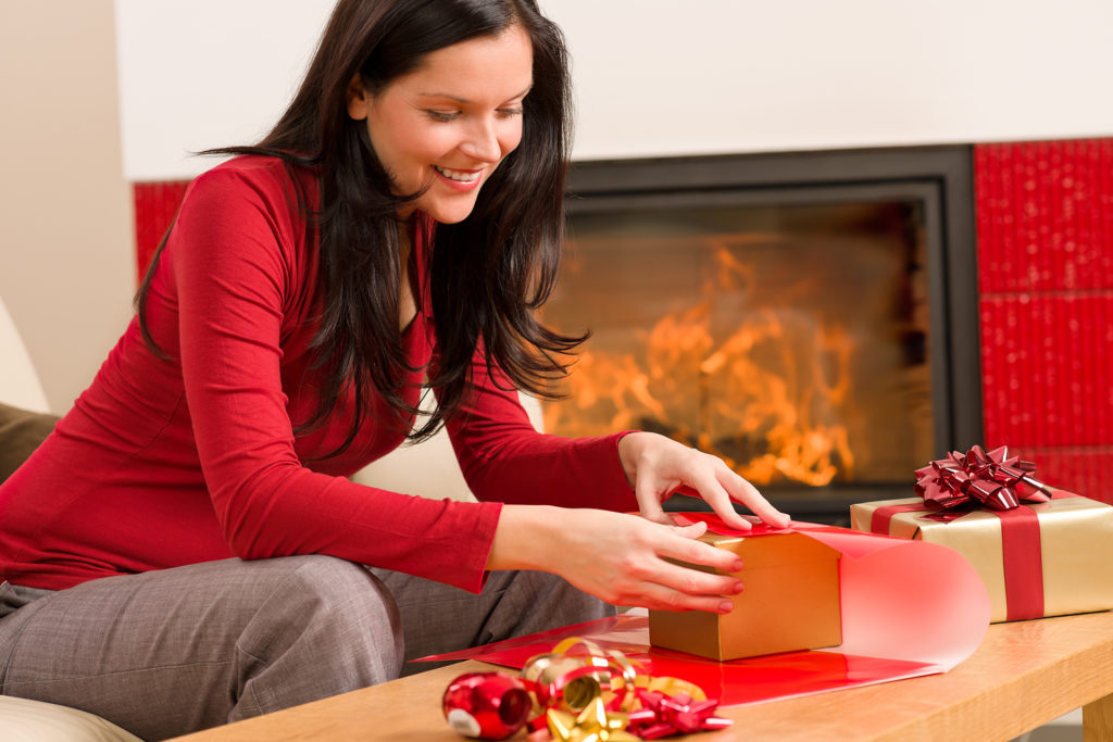 Happy woman in red wrapping Christmas present by home fireplace;