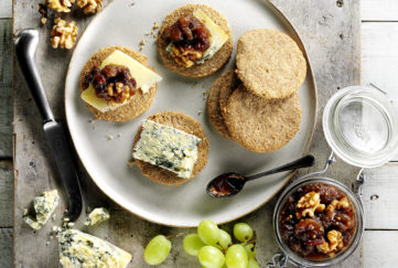 Plate of oatcakes with cheese, grapes and jar of home made chutney