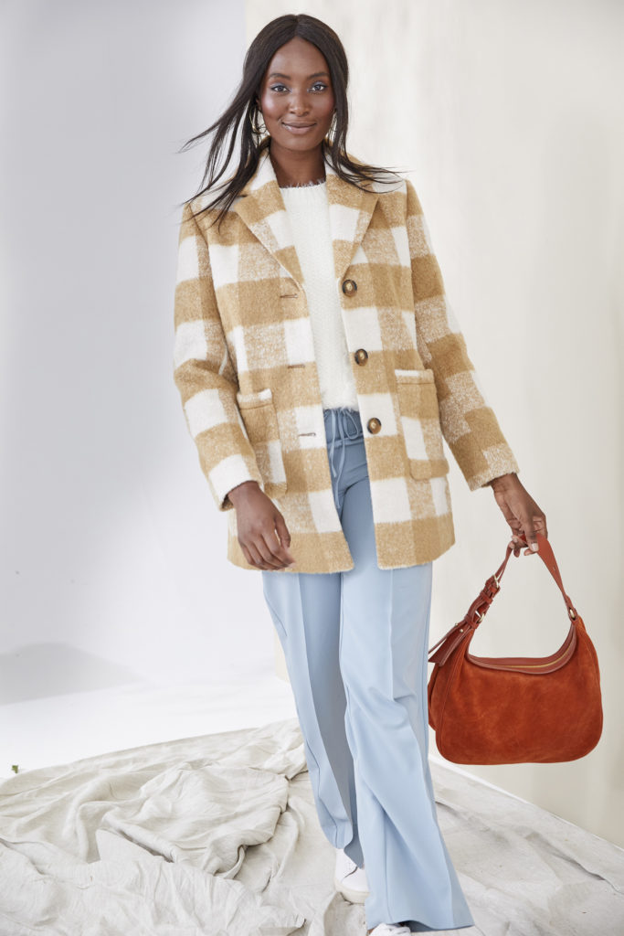 Model wearing beige and white bungalow check jacket over white top and pale blue trousers, large red bag