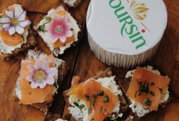 Pack of Boursin soft cheese and 5 small squares topped with soft cheese, smoked salmon, herbs and edible flowers on rustic wooden table