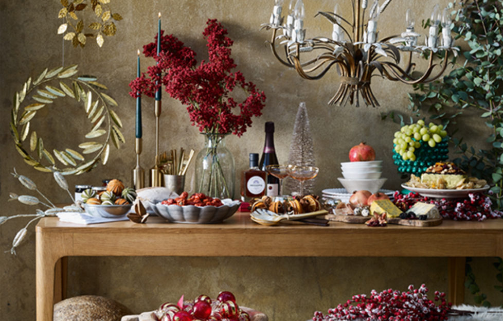 Table with plates of food, candles, decorative branches with berries, gold leaves and rustic light fitting