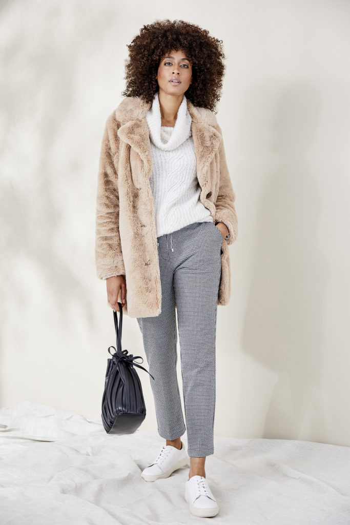 Model in cosy faux fur jacket teddy bear style in soft beige, over white cowl neck jumper and smart grey trousers, carrying dark blue bag