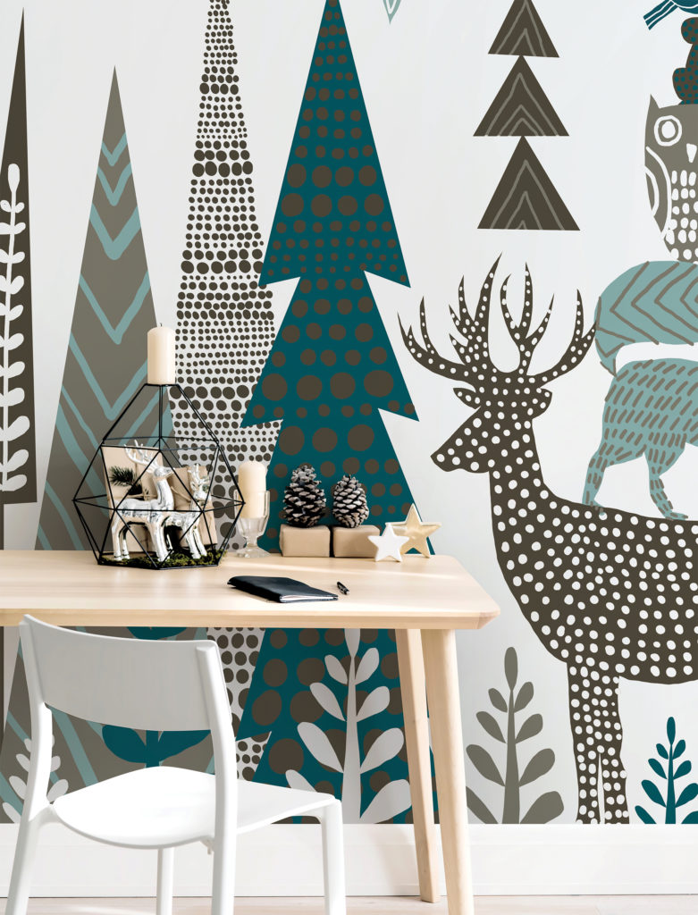 Desk and chair against a wall decorated with large green, black and white stylised deer and fir trees