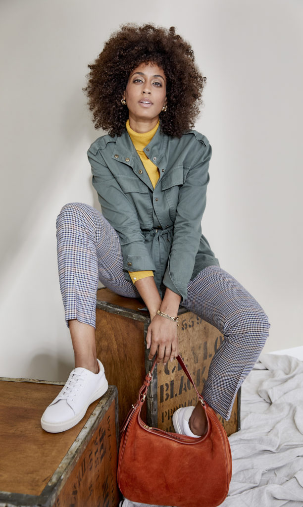 Model in light teal belted jacket over yellow top with fine check trousers and white tennis pumps
