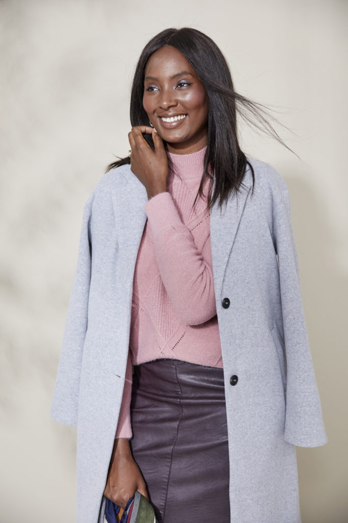 Model in lilac grey felt coat, lapels and 2 buttons, over pink textured jumper and purple leather skirt