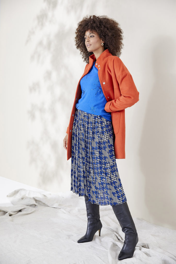 Model in blue patterned midi skirt, royal blue top and orange thigh length coat