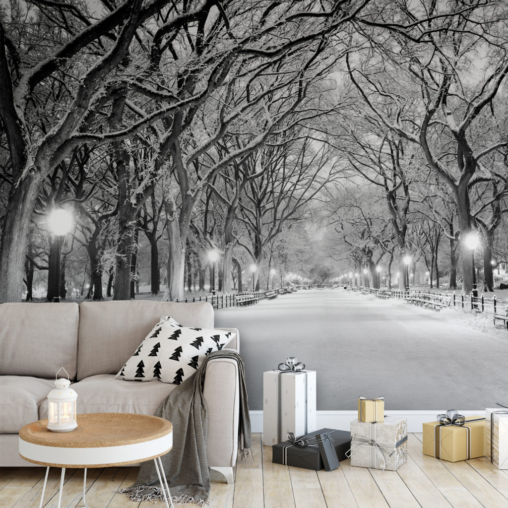 Stylish grey sofa and wrapped gifts, wallpaper of a snowy path and shining street lamps, bare black trees arching overhead