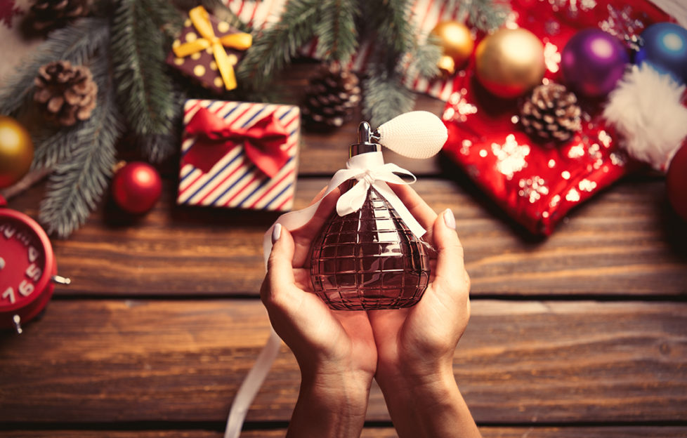 Perfume in hand with Christmas background Pic: Shutterstock