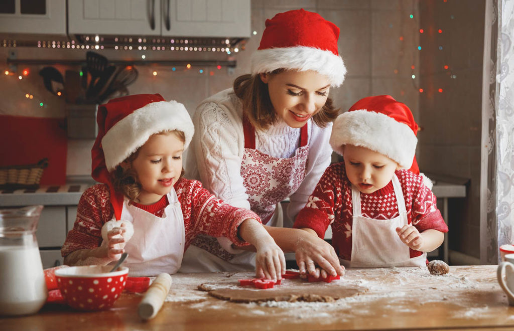 Mum baking with two young kids Pic: Shutterstock