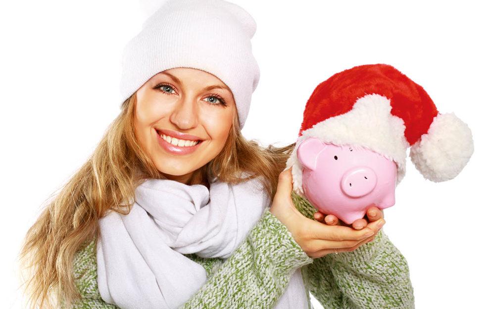 Lady holding piggy bank wearing santa hat Pic: Shutterstock