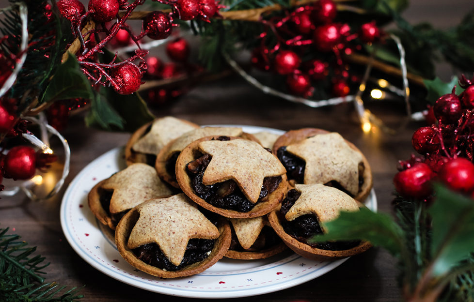 Plate of home made mince pies topped with pastry stars, red berry decorations behind