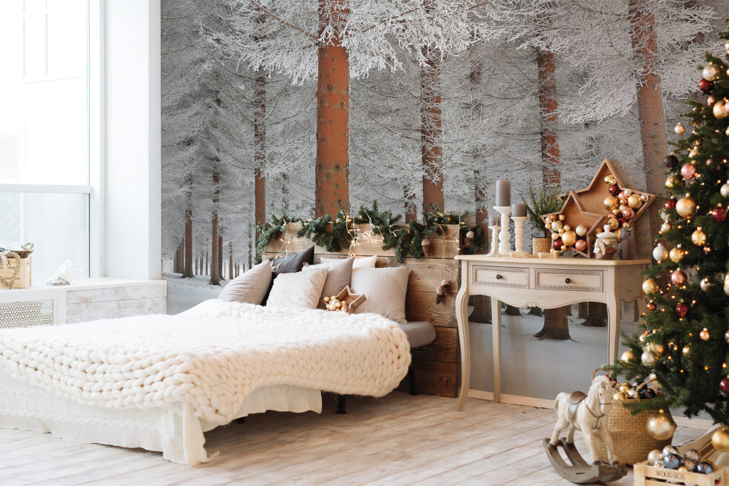 Stylish bedroom, laminate floor, white linen and wall mural of snowy larch trees, lacy branches and red trunks