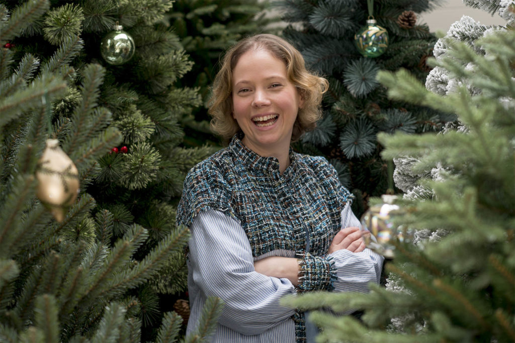 Young woman laughing, standing amongst tall real Christmas trees, few baubles