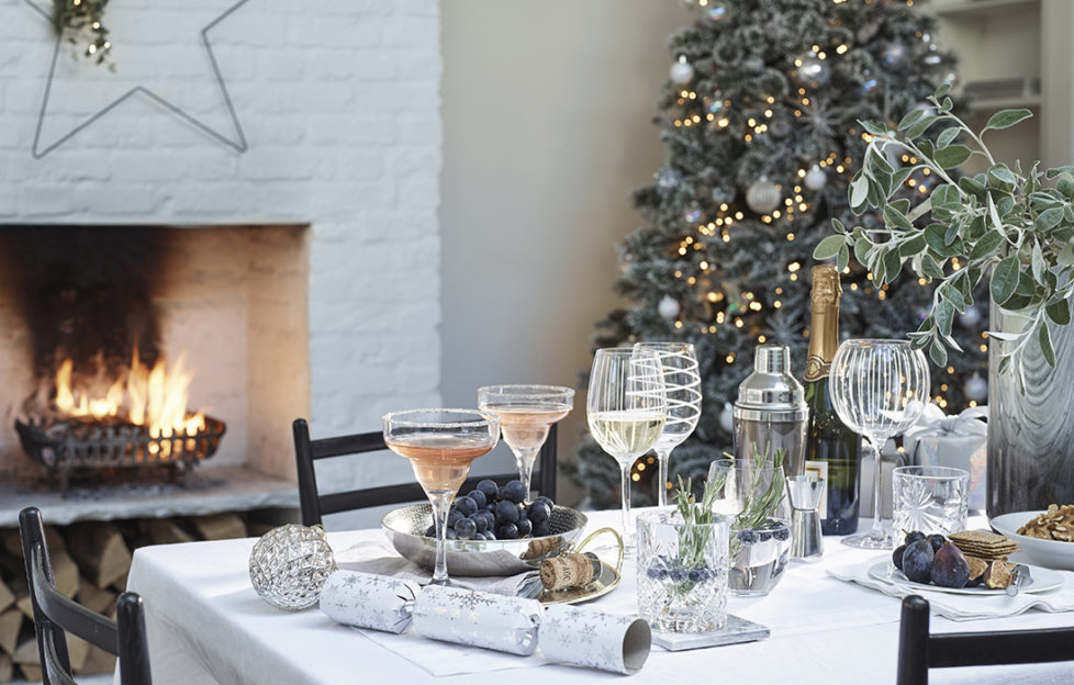 Table set for Christmas dinner with decorated wine glasses and crackers, frost themed Christmas tree behind