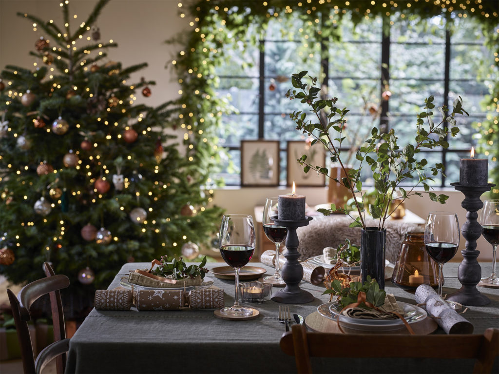 Table with candlesticks and wine glasses, large green tree and green window garland both dotted with white fairy lights