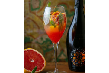 Wineglass of glowing reddish-orange drink with citrus slices and sage leaves