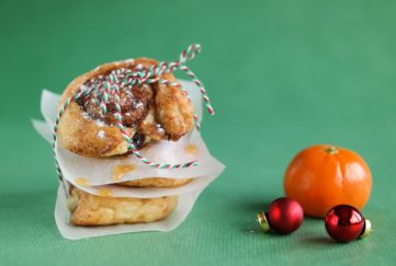 3 cinnamon swirls pastries loosely wrapped in greaseproof paper, tied with red/white/green twisted string, tangerine and baubles on green background