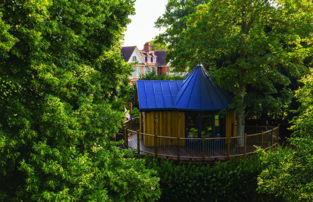 Blue roofed treehouse accommodation with circular platform, hotel beyond