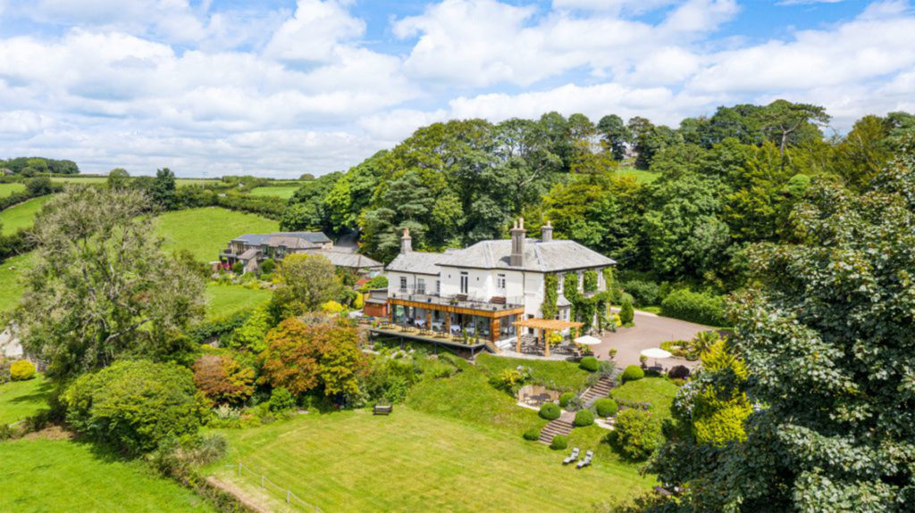 Large house set in lush countryside, looking down from high angle
