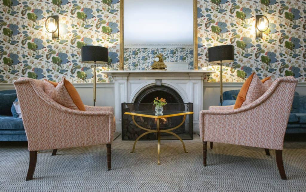 2 chairs and table by fireplace, elegant wallpaper in large floral and leafy design
