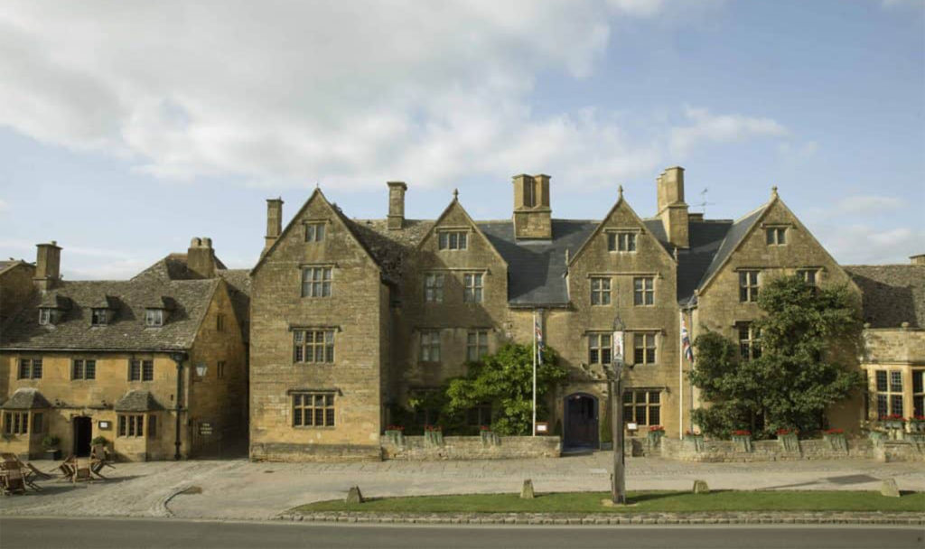 Traditional yellow/grey stone building, stone mullioned windows and tall chimneys
