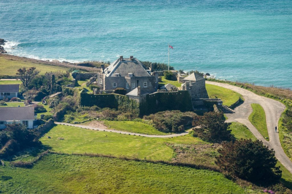 Looking down on to grey stone castle, sea beyond