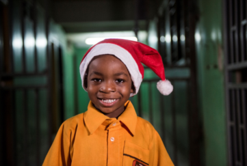 A young boy in a Santa hat
