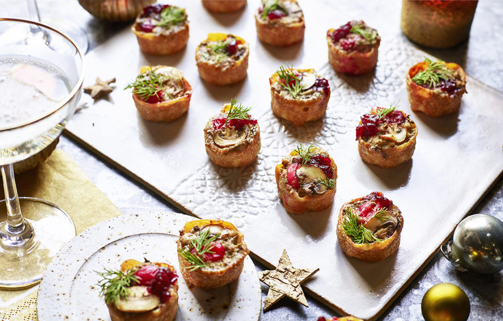 Christmas canapes on a board with dill sprigs and mushrooms